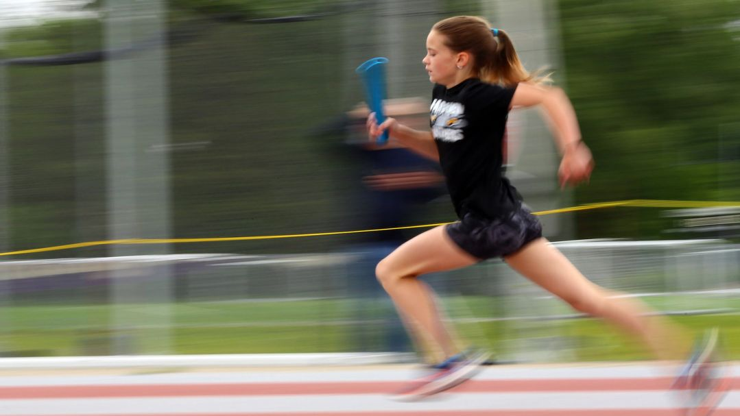 A young woman in blurred motion, running relay on a track.
