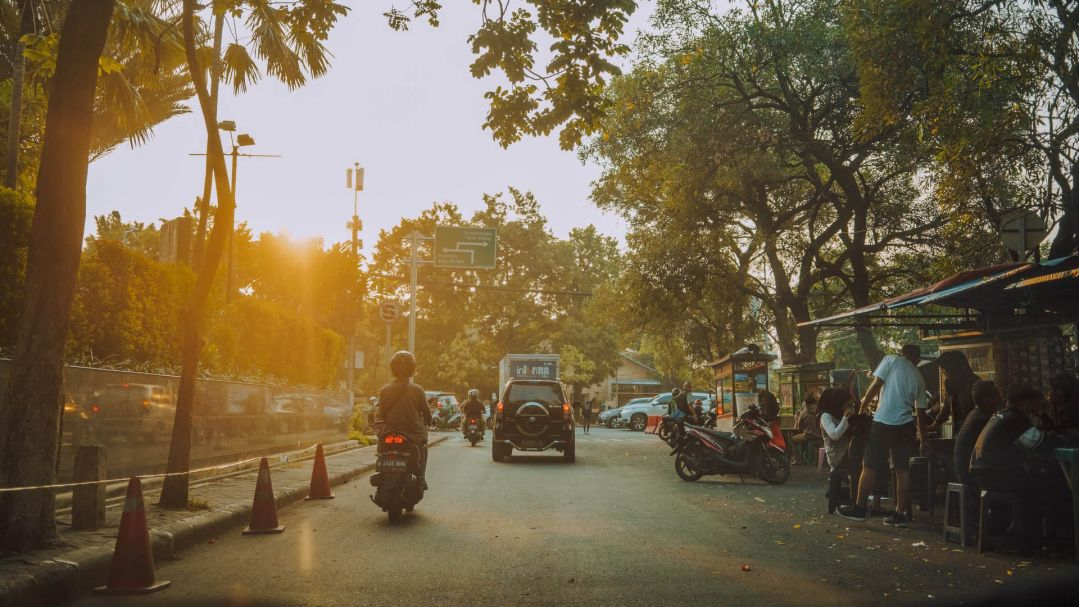 A busy Jarkarta street at sunset, with people eating outdoors and riding motorbikes
