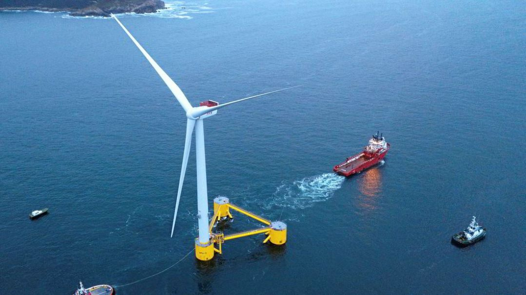 A floating wind turbine in the ocean with tugboats around it