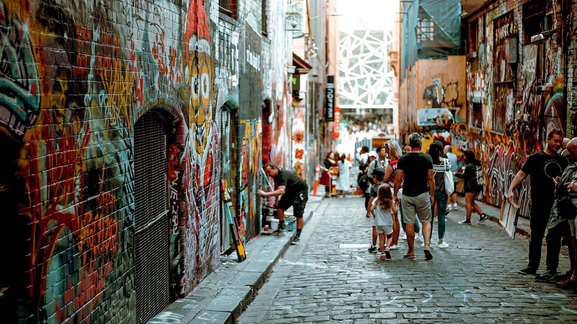 People view street artists in action in one of Melbourne's popular art laneways. Picture: Annie Spratt.
