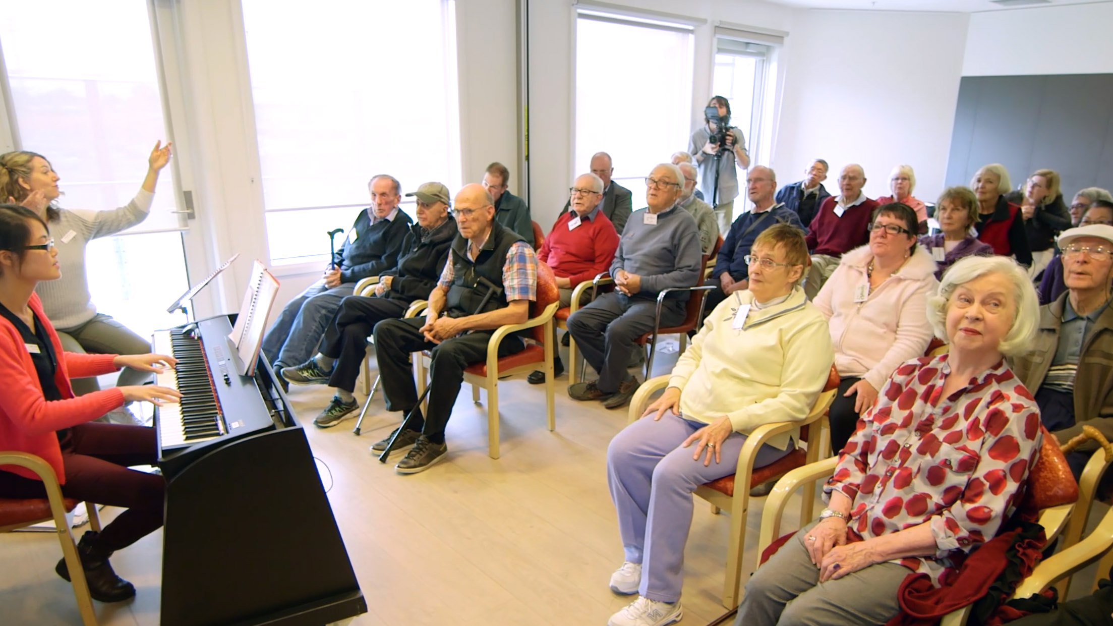 ParkinSong participants and music therapists at a seated group choir session