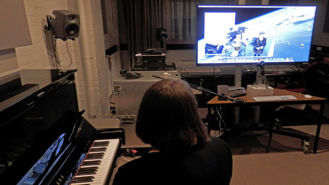 A woman sits at a piano in a music studio, talking into a microphone. A student is displayed on a projection screen.