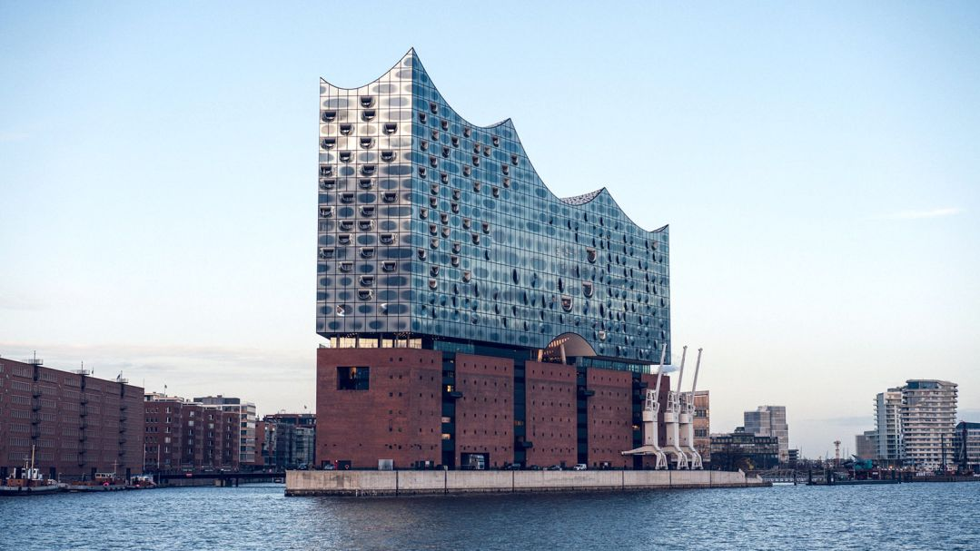 A contemporary building on the edge of a river. It has a brick base and the top is scalloped and made of glass.