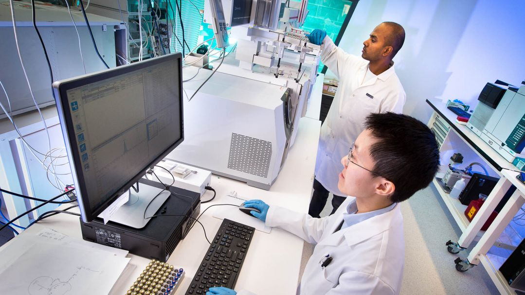 Two men in a lab wearing white lab coats. One man is using a computer, the other is checking a machine.