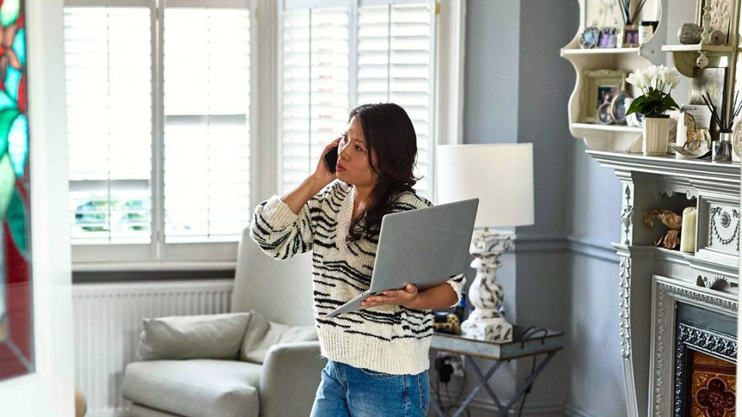 A woman in her loungeroom holding a laptop and talking on the phone