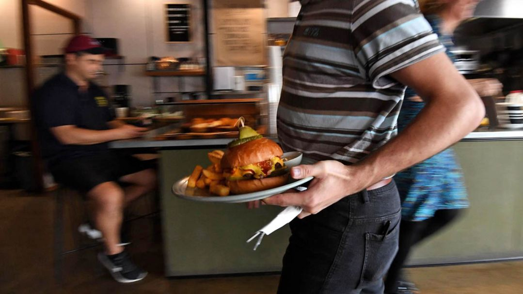 A man holding a burger on a plate walking through a busy cafe