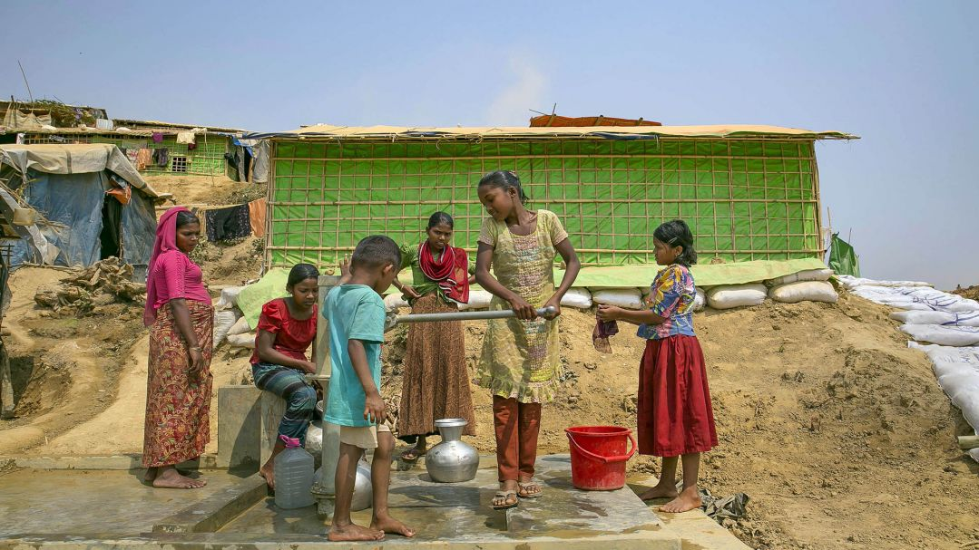 Girls pump water in Balukhali refugee camp