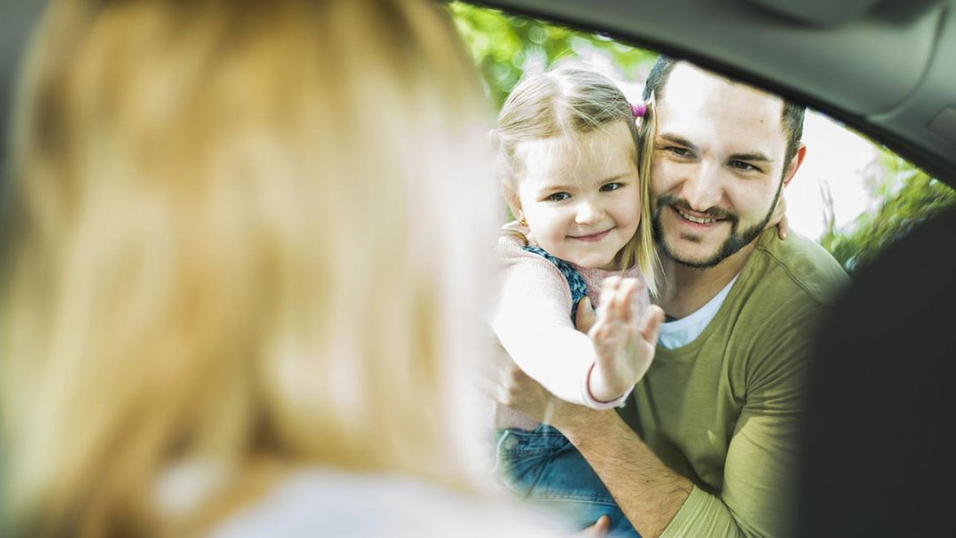 Mum sitting in the car, dad holds a child as she leans in the window of the car to wave