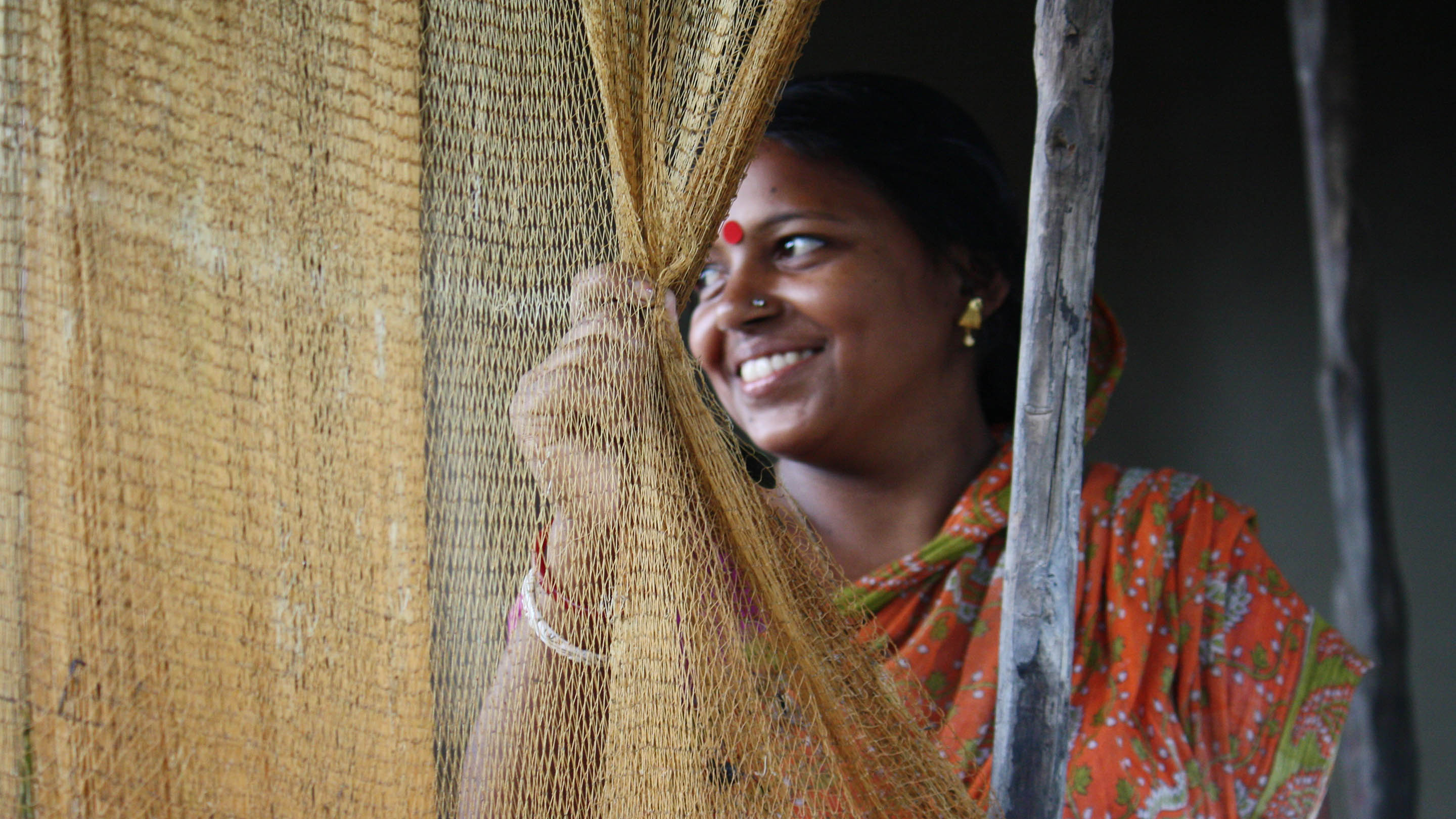 A young woman from a fishing community in West Bengal pulls a fishing net to one side