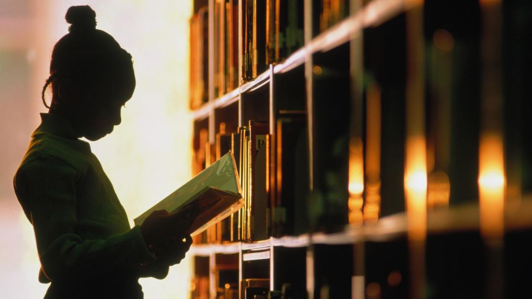 A young girl in silhouette holding a book beside a library shelf