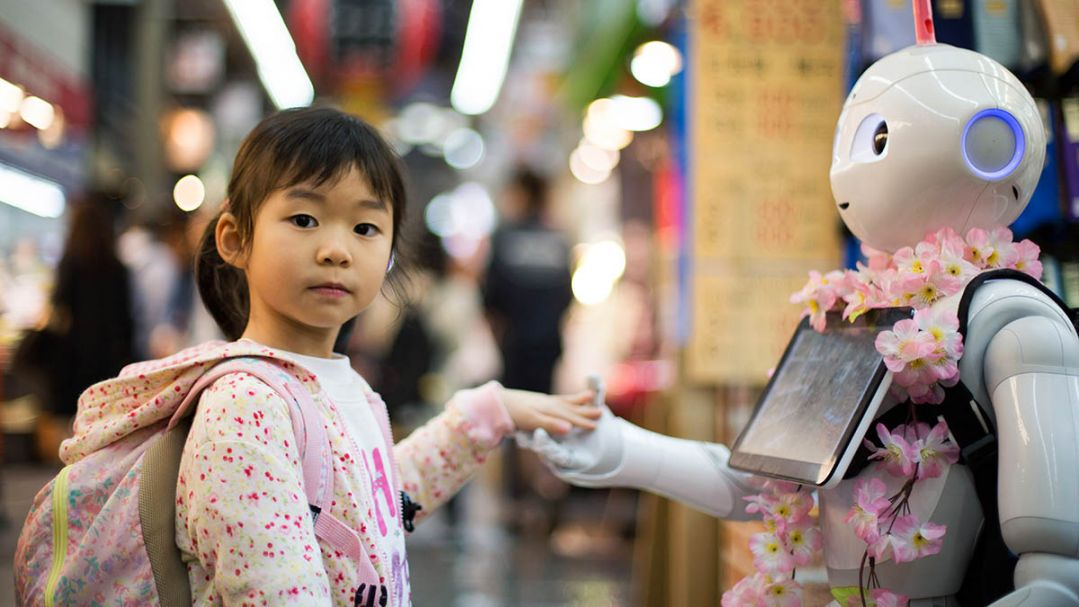 A young girl wearing a backpack holding hands with a smart robot