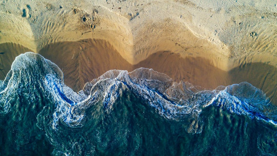 aerial view of waves crashing onto a yellow sandy beach