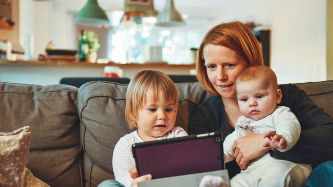 A mum sitting on the couch with her baby and toddler looking at an ipad