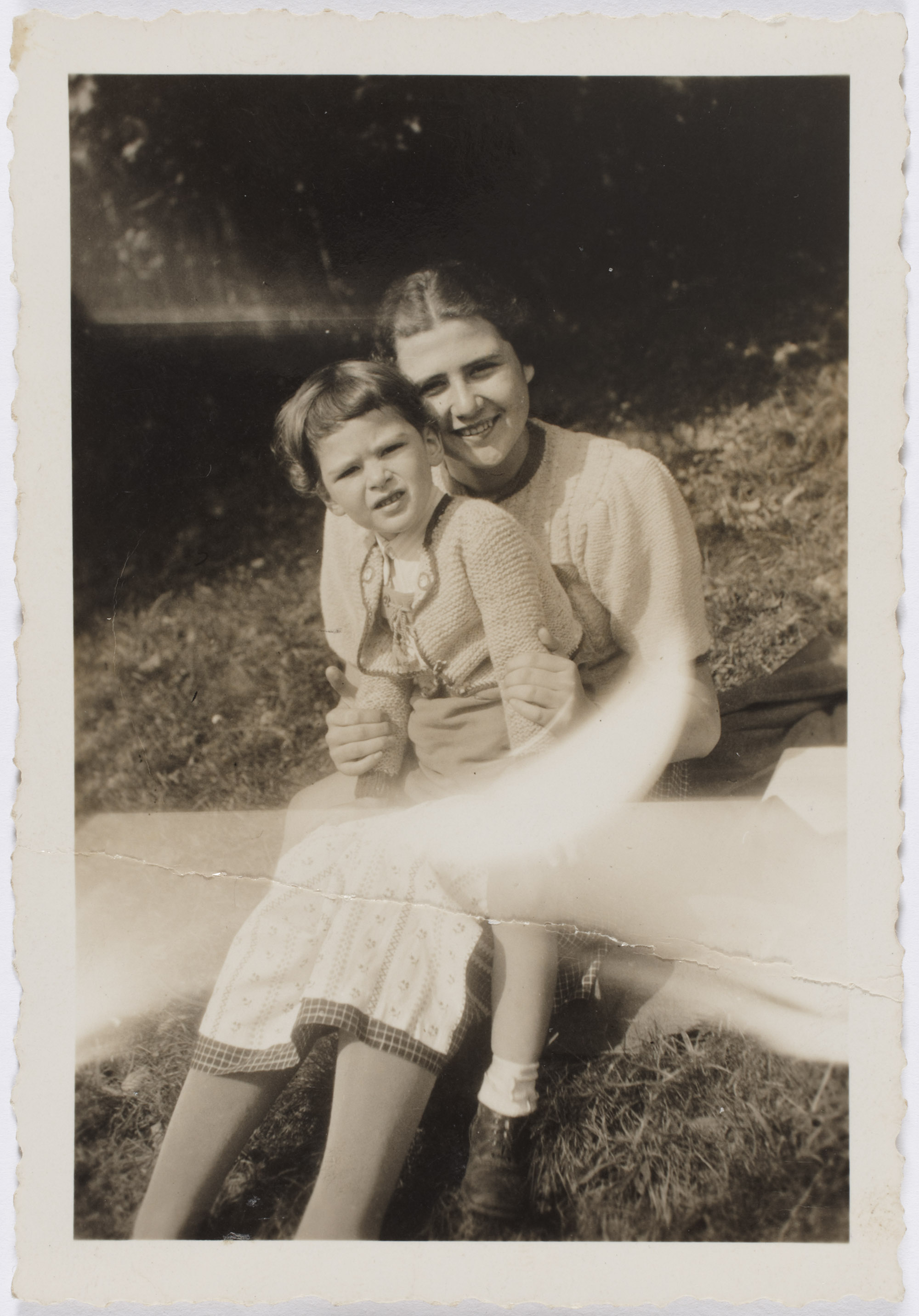 A faded B&W photograph of Edith Roll kneels with her brother fritz in her lap.