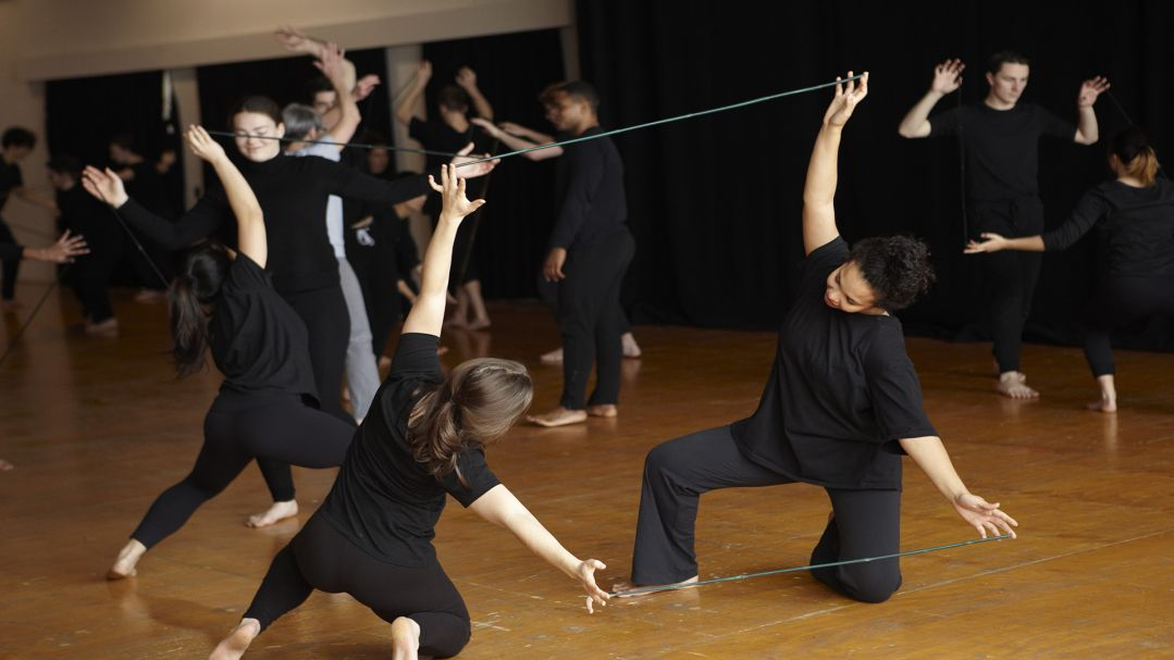 people in black outfits doing performative dance on a wood floor dance studio