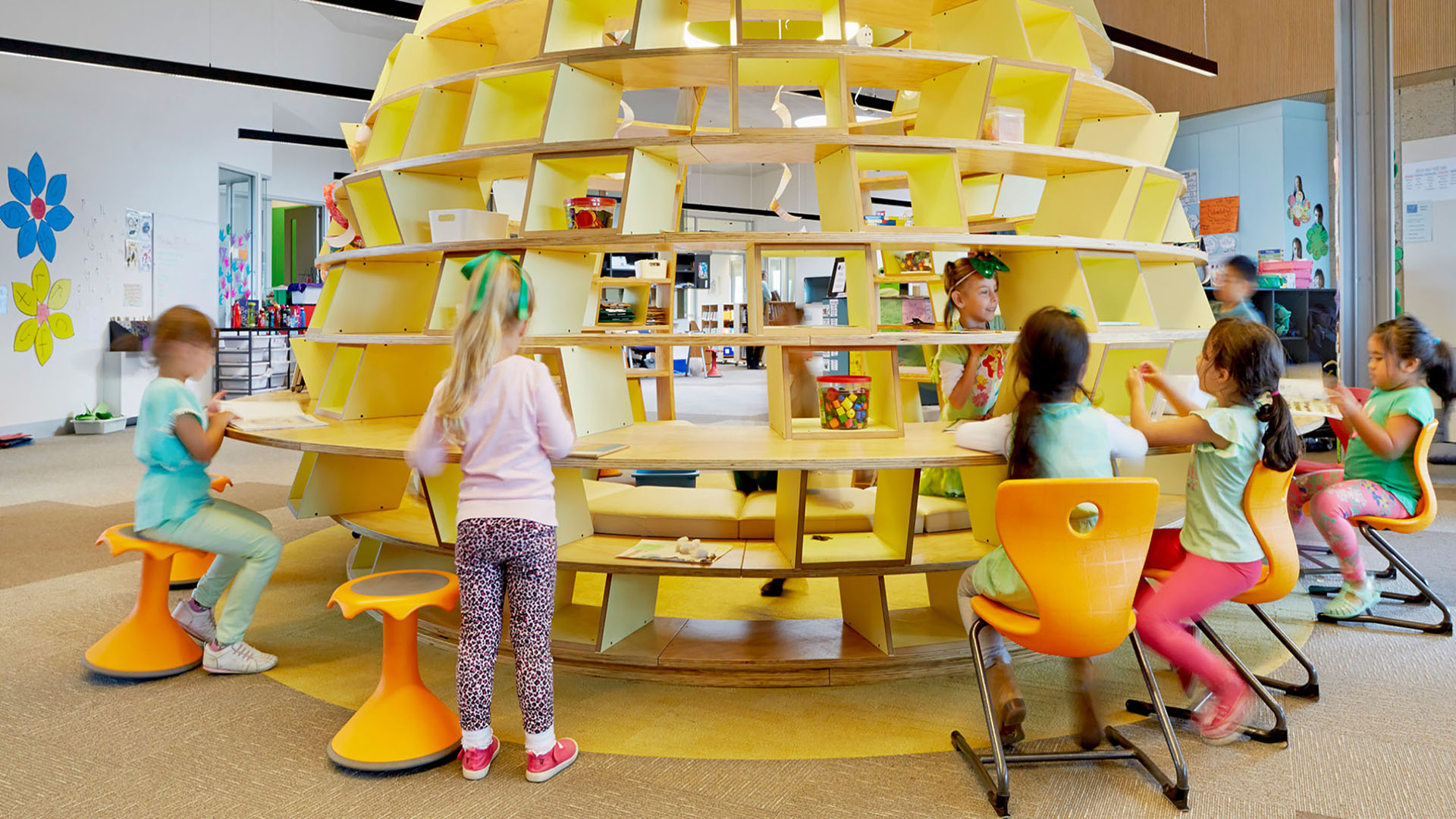 Kids sitting at and playing around a yellow beehive structure in their classroom