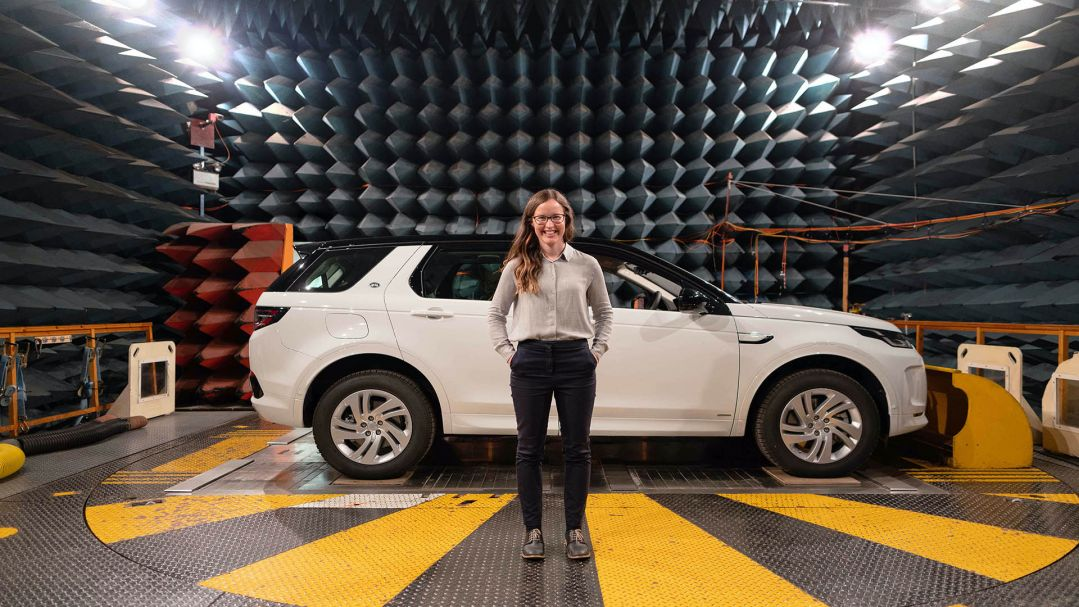 A woman standing on a rotating metal platform in front of a white car