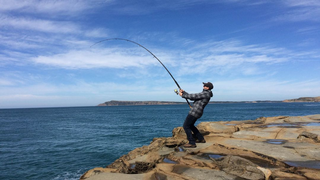 A man standing on rocks by the ocean reeling in a fish on his fishing rod