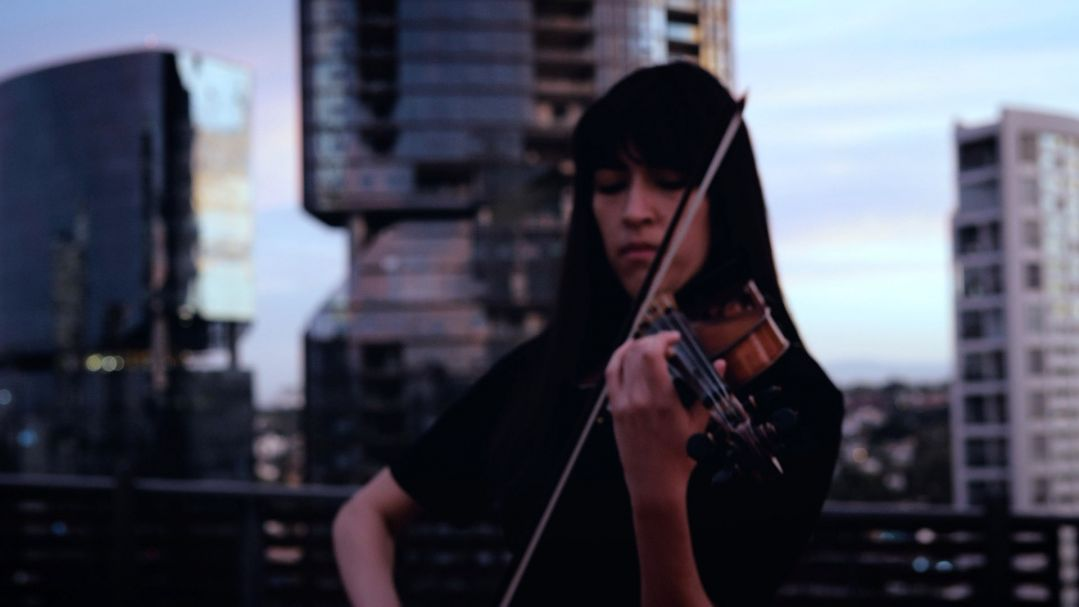A woman from mixit plays a violin against a background of skyscrapers