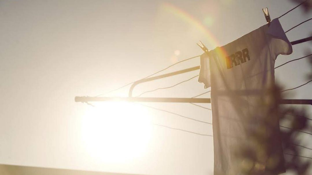 A t-shirt with the letters RRR on it, hanging on a hills hoist. The sun is setting behind.