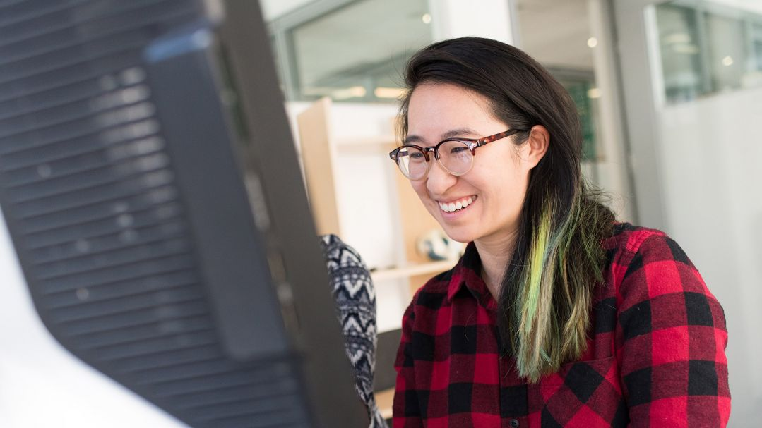 A woman using a desktop computer. She has long brown hair dyed green at the ends and is wearing a red and black check shirt