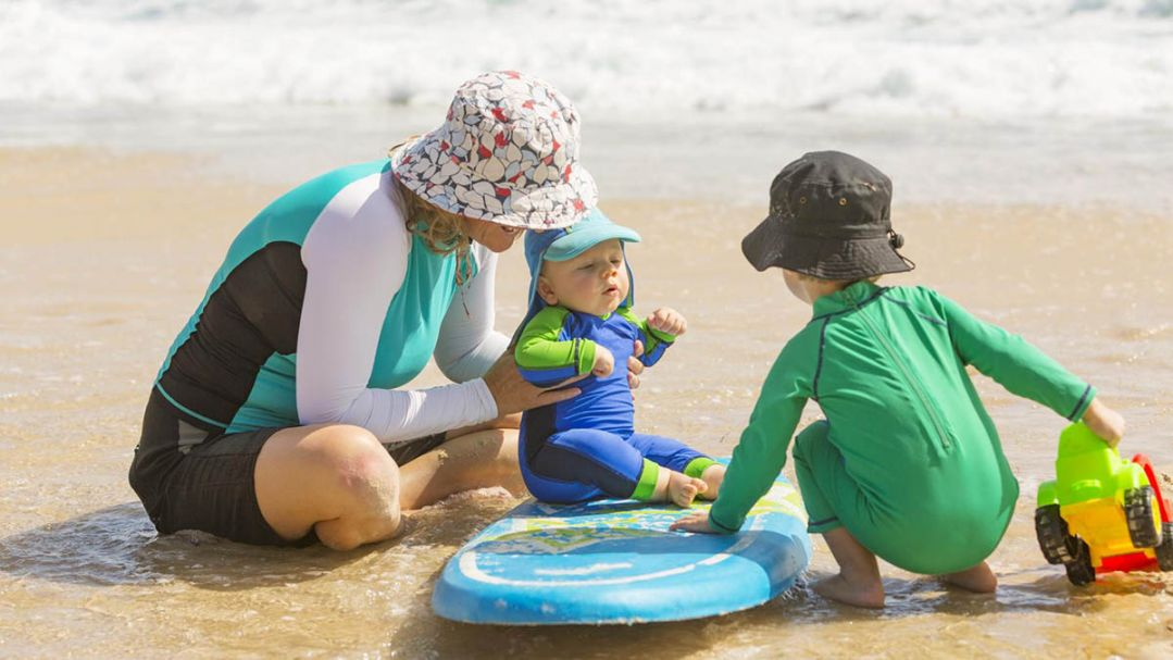 A woman and two young children playing on the beach. They are wearing sun smart clothing and hats
