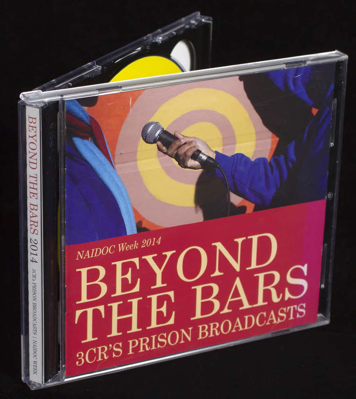 CD cover for Beyond the Bars 2014, with a person in a hoodie interviewing another person in front of a colourful artwork