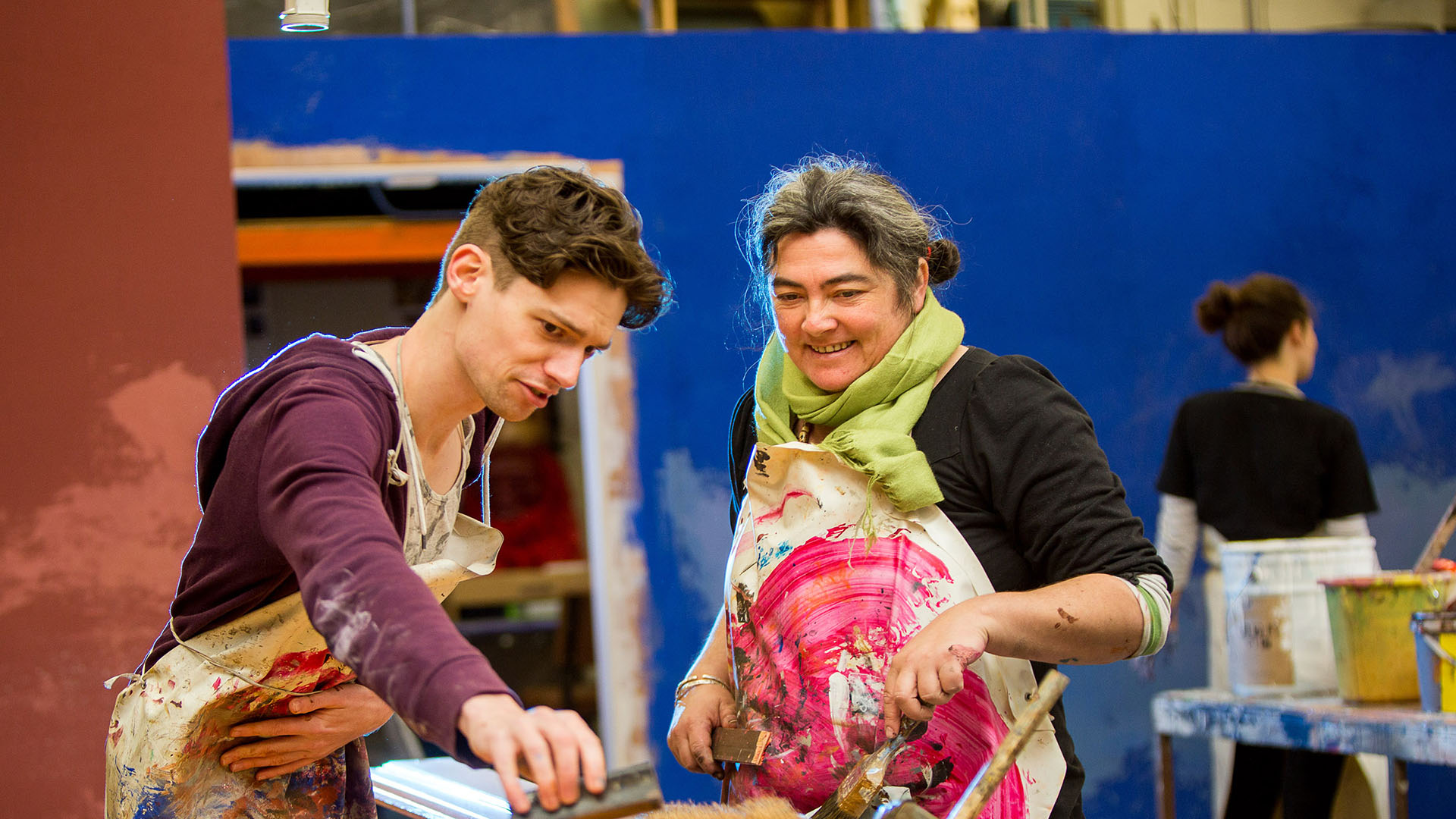 A woman and a man are creating artwork on a workbench