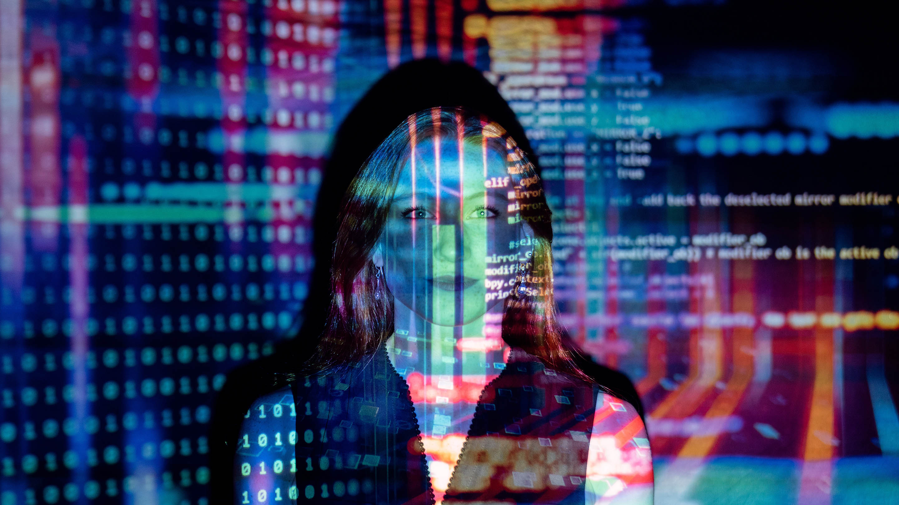 Computer code and lights projected over a woman's face