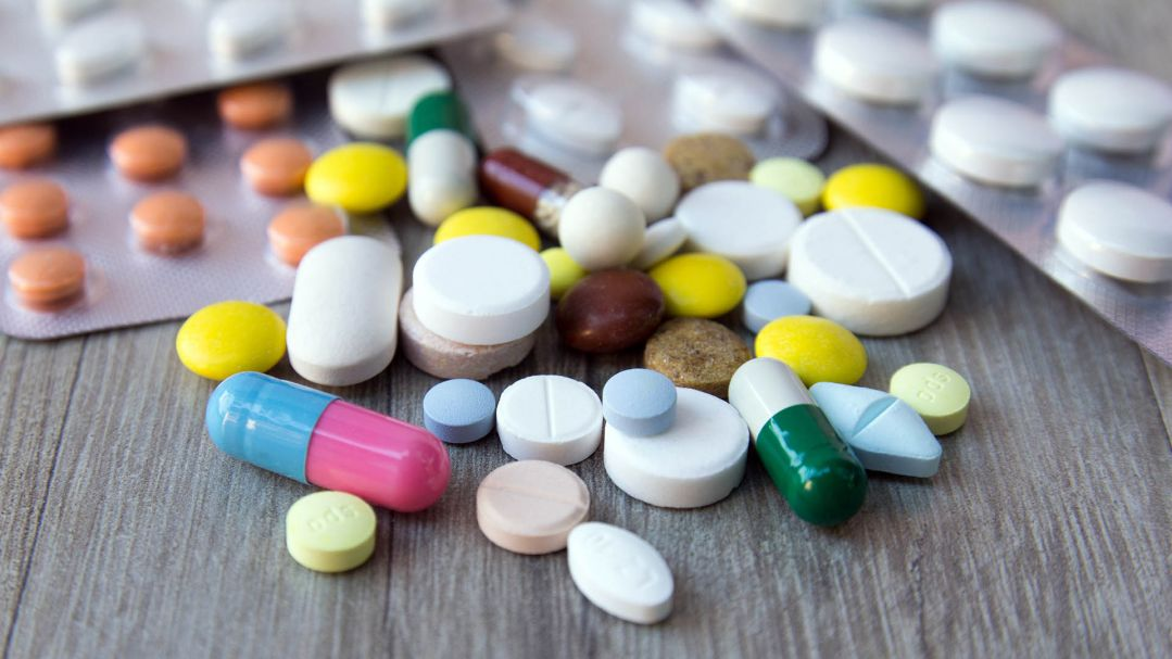A number of pill packets and loose pills of different shapes and colours