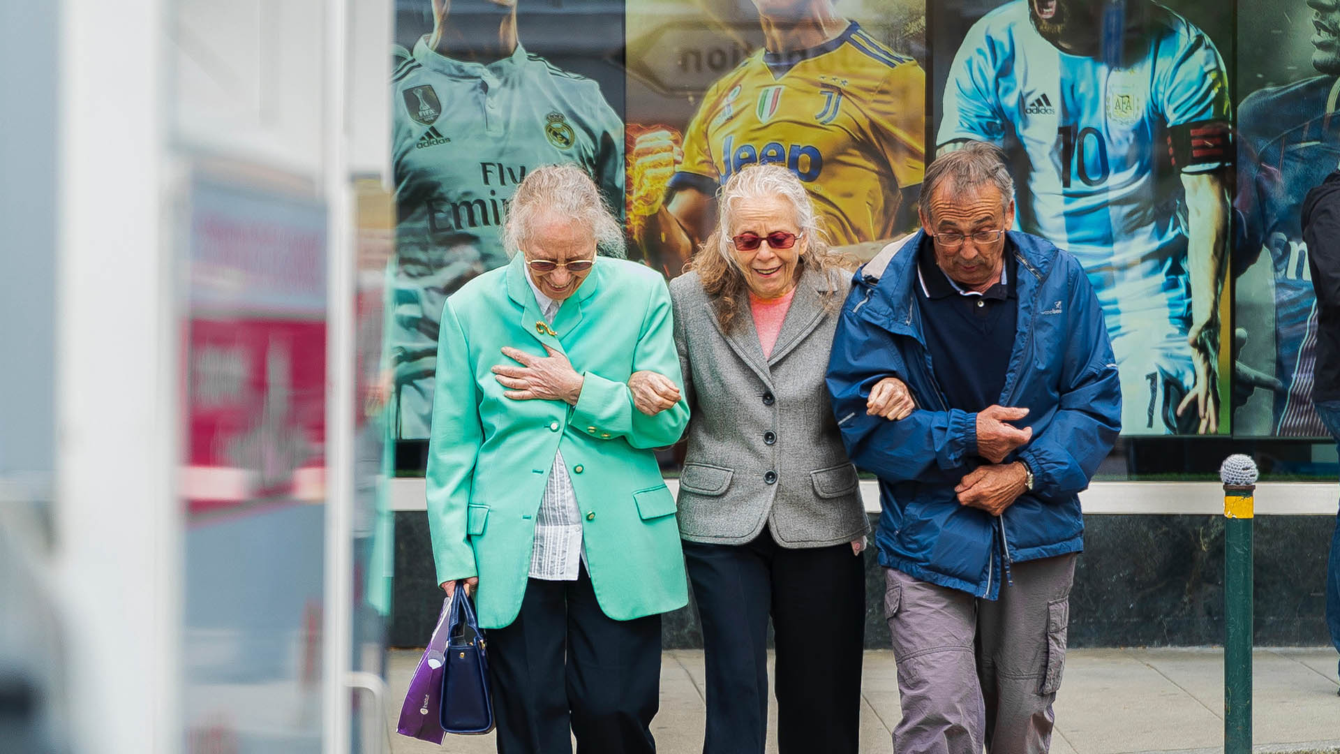 three older people linking arms and walking down the street