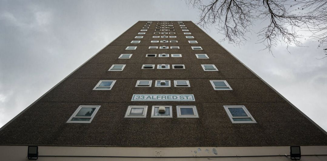 A view looking up at a public housing building. The address on the building says 33 Alfred Street.