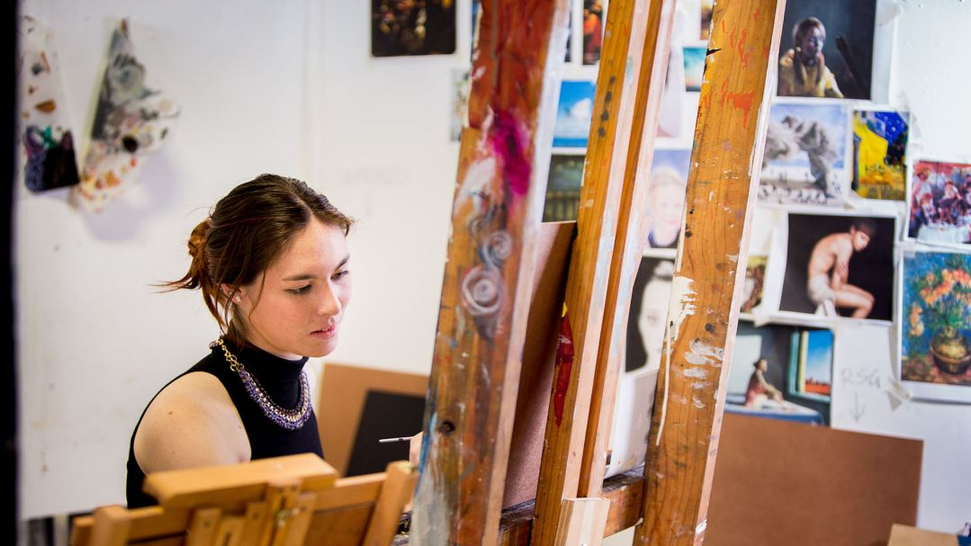 An artist working at an easel in their studio