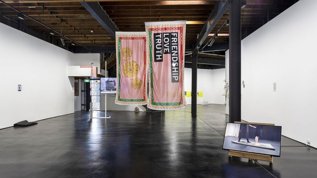 An installation view of an exhibition with two hanging textile works and a screen on the floor in foreground