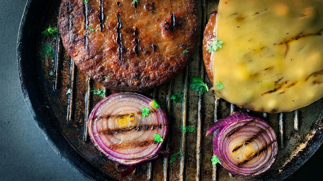 A plant-based burger in a cast iron pan with cheese and red onion