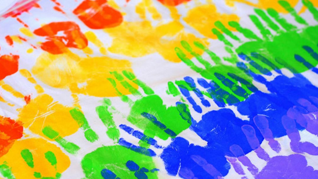 Children's handprints painted in rainbow colours