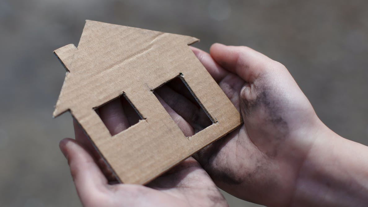 A person holds a cardboard facade of a house in their hands