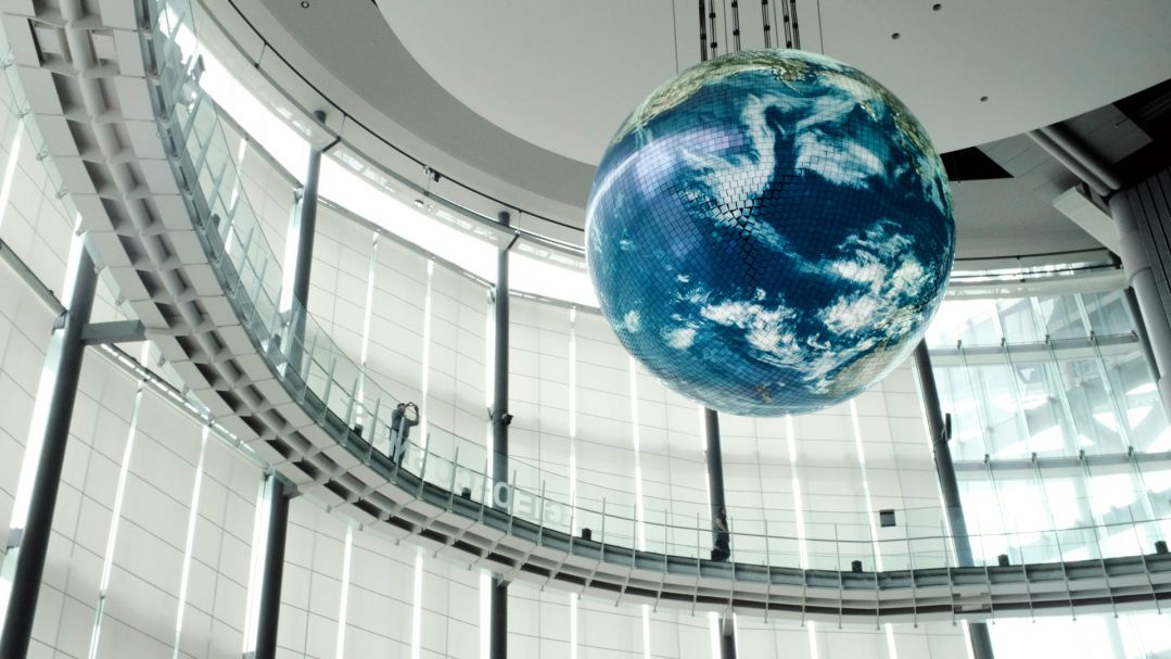 A large building atrium with floor to ceiling glass windows, a curved walkway and large suspended figure of the globe