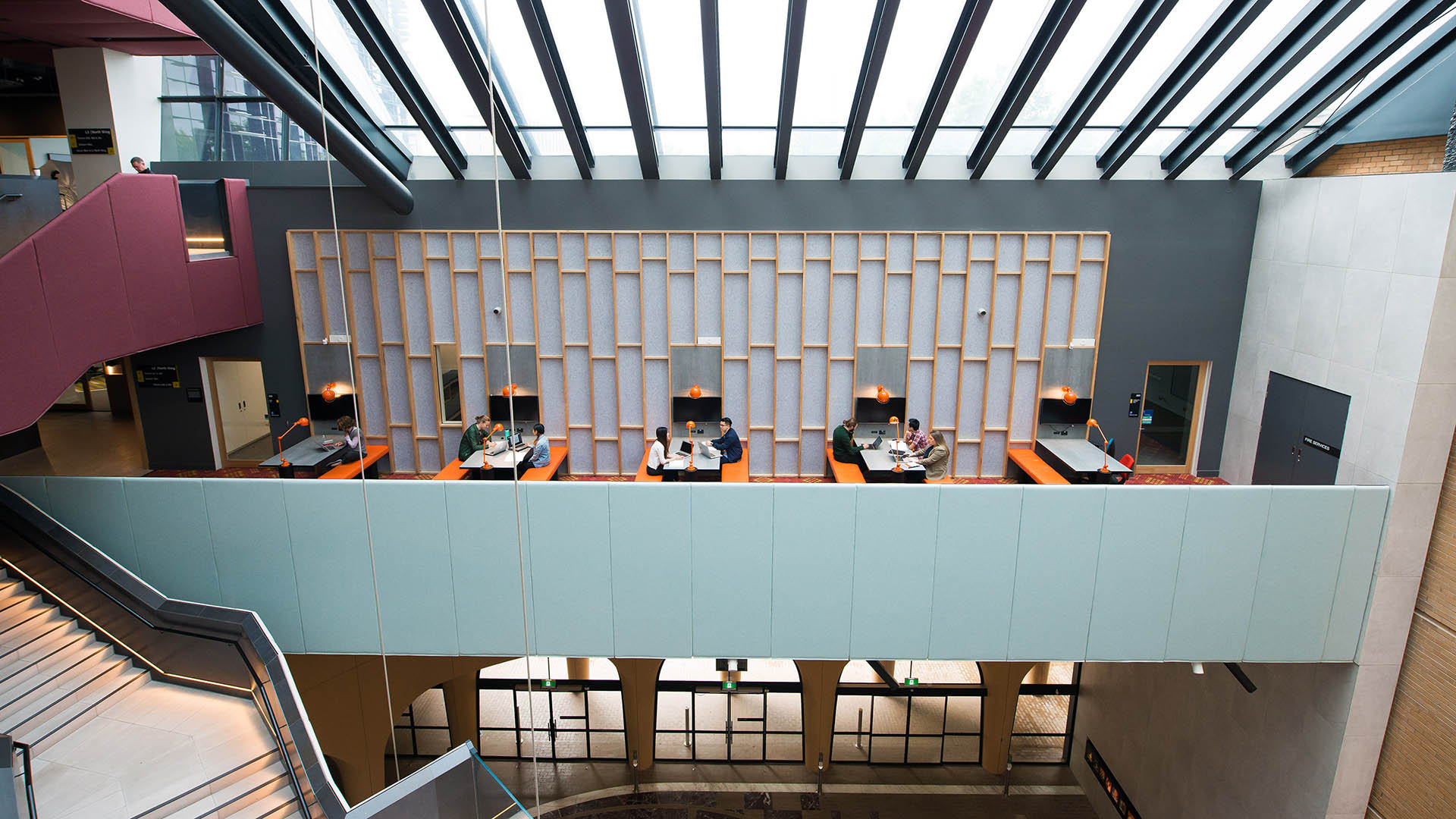 * interior of a building it has light filled beamed roof and a mezzanine with desks and chairs