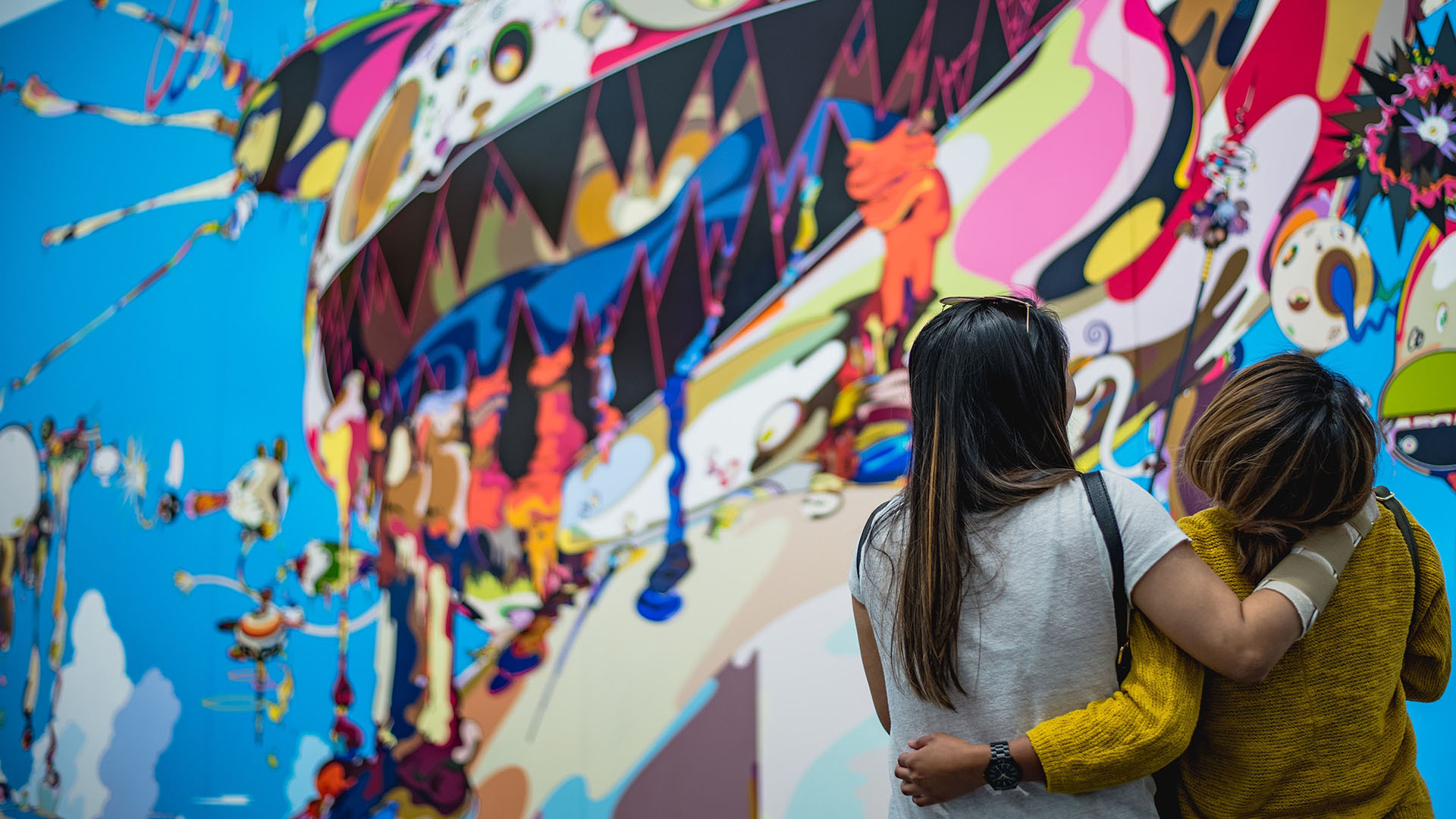 Two women stading facing a colourful street mural