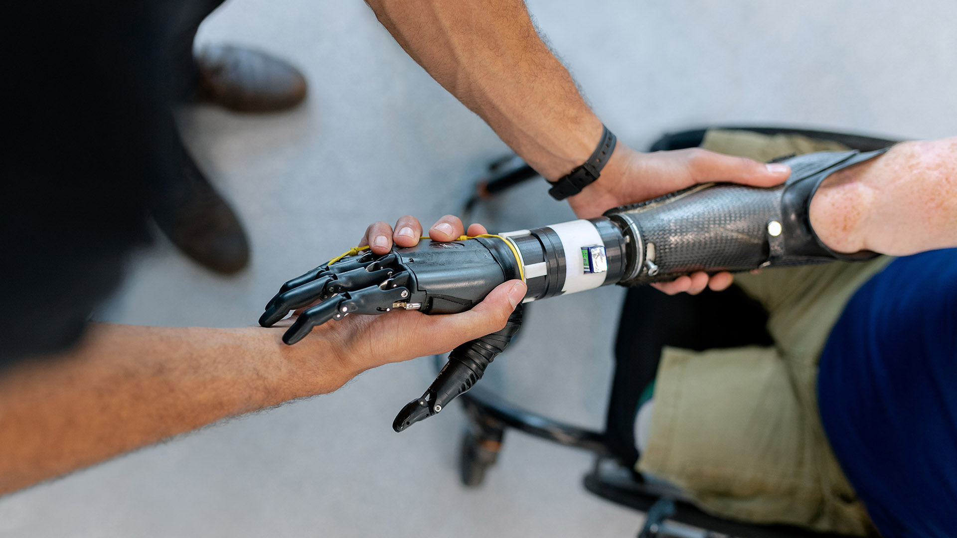 bioengineered arm for person with disability. The person is sitting on a wheelchair.