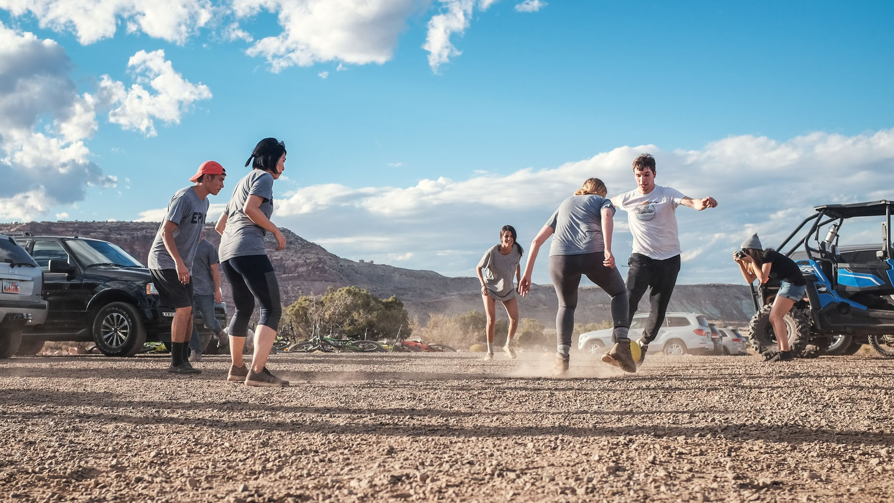 A group of young men and women playing soccer in a desert carpark