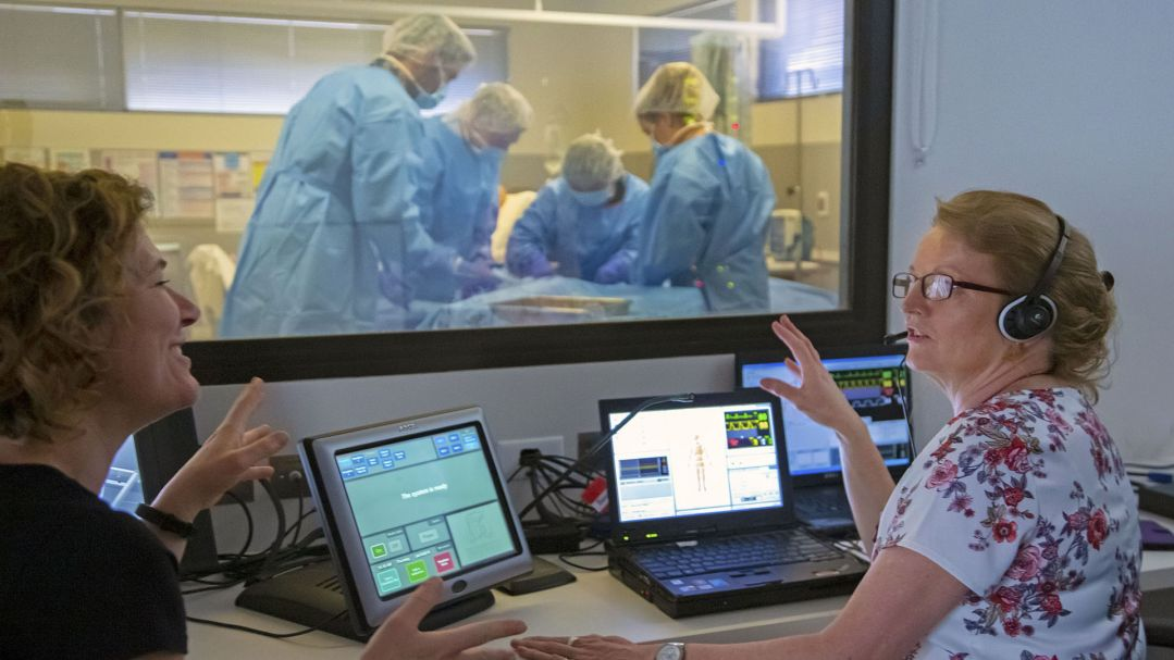 Two women sit next to computers and observe a surgical procedure