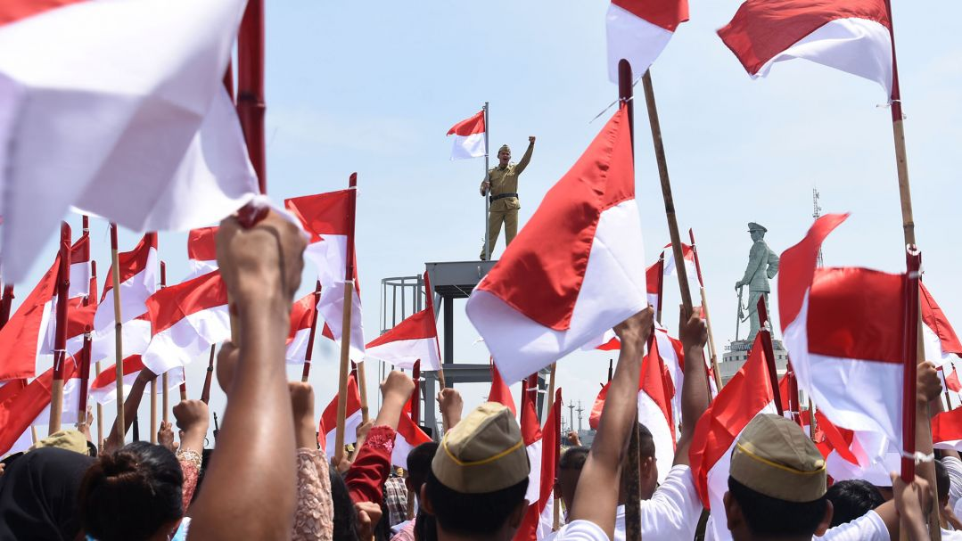 A man stands on a platform with his fist raised with a crowd of people waving flags in the foreground. Image: M Risyal Hidayat / Antara