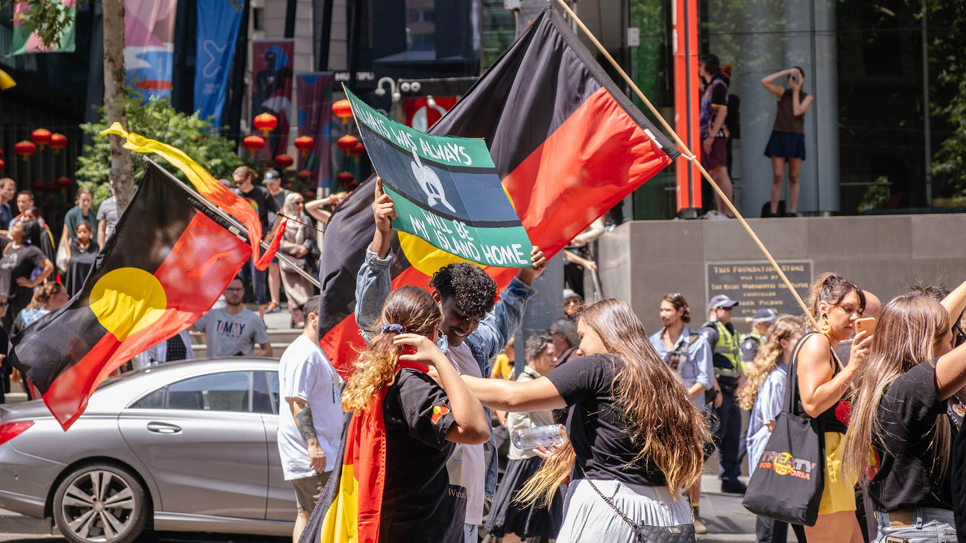 Marchers and young Indigenous people at the Invasion Day rally in Melbourne Australia waving Aboriginal and Torres Strait Islander flags