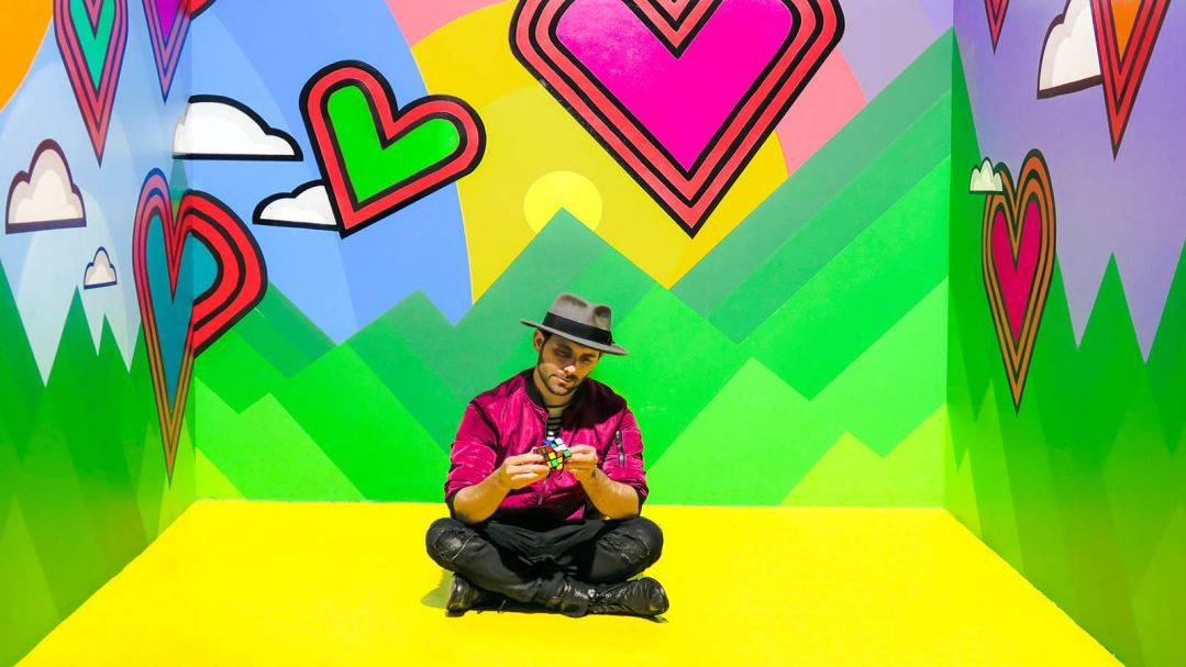 A man sitting in a room with colourful mural of hearts and clouds. He's playing with a Rubik's cube.
