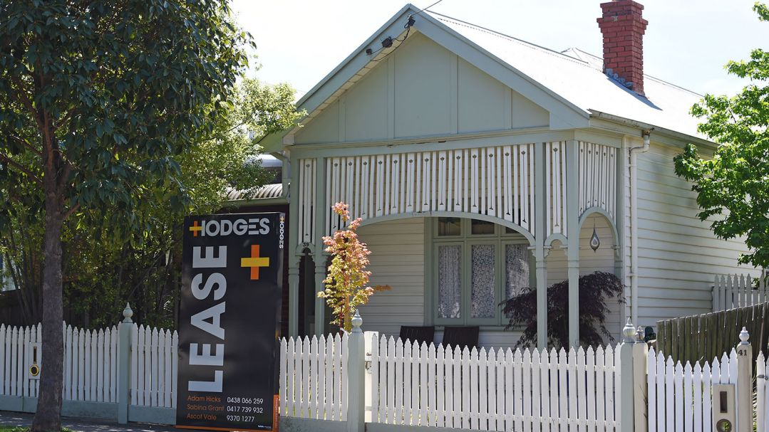 The front view of a wetherboard house. It has a white picket fence and a For Lease sign.