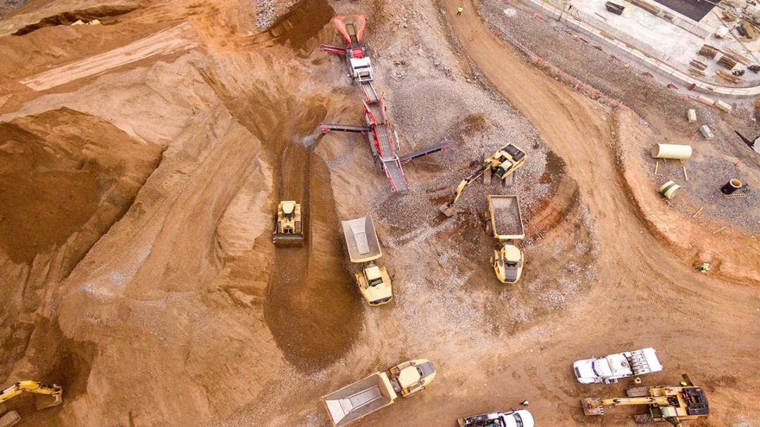 arial view of trucks and plant equipment on a large open cut quarry