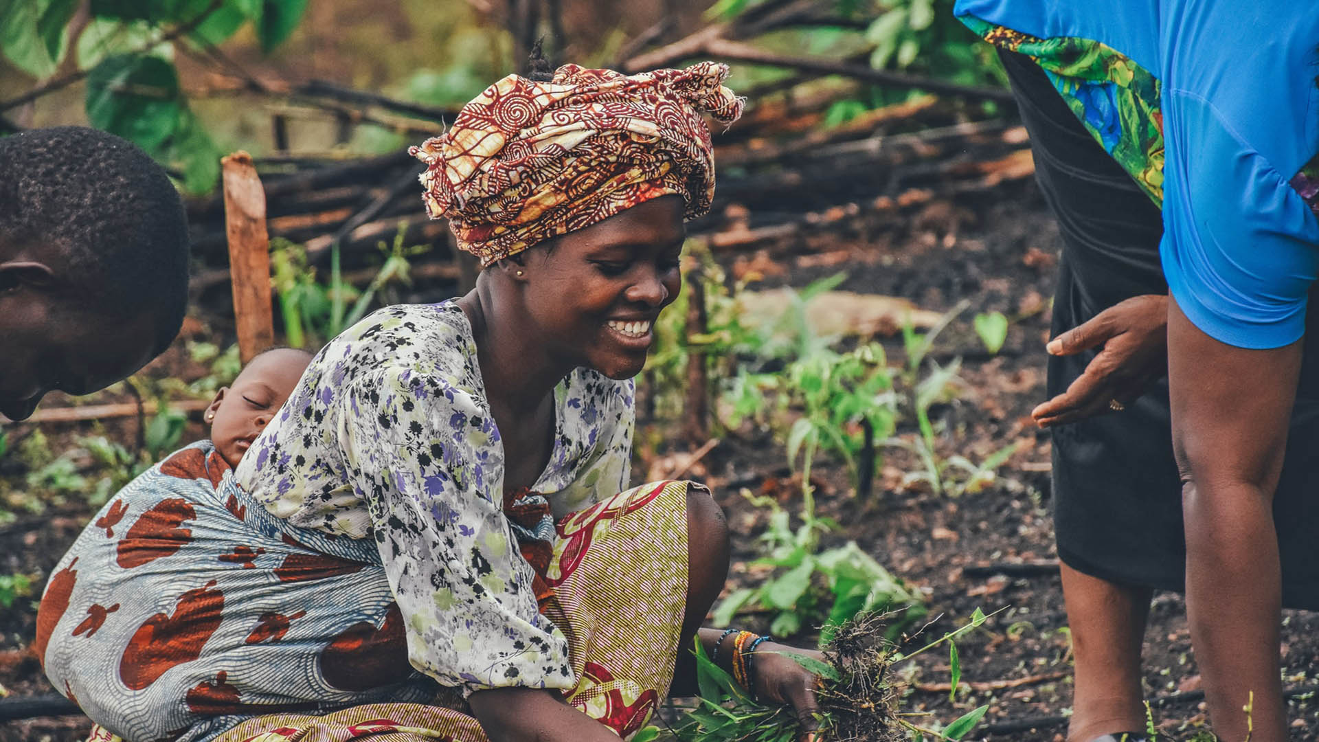 A woman in a head wrap tends to a field. There is a baby in a sling on her back.