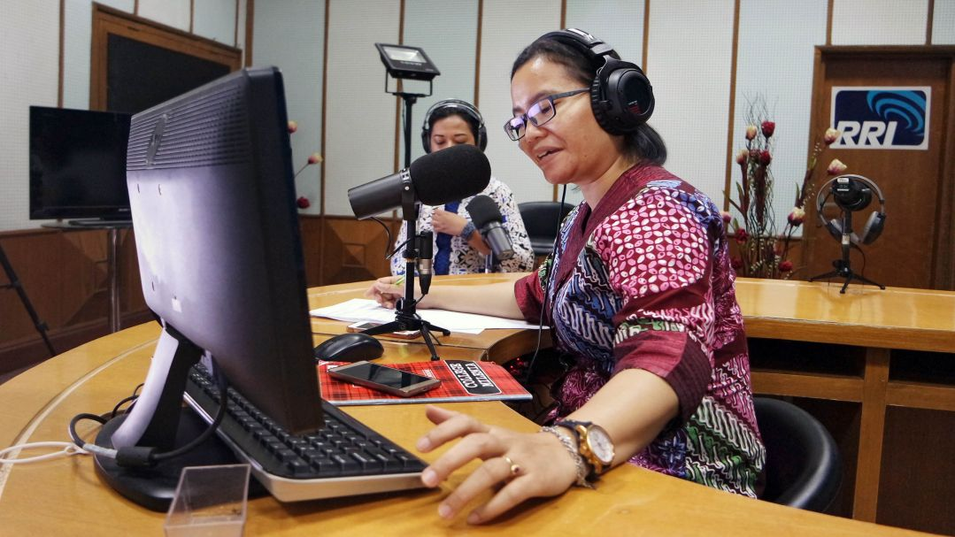 A woman talks into a microphone at a community radio station